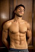 Sexy handsome young man standing shirtless in his bedroom against wooden wardrobe door poster