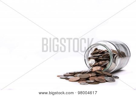 British one penny coins flowing from a glass jar