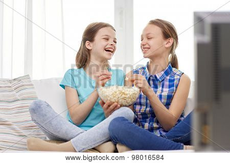 people, children, friends and friendship concept - two happy little girls watching tv, laughing and eating popcorn at home