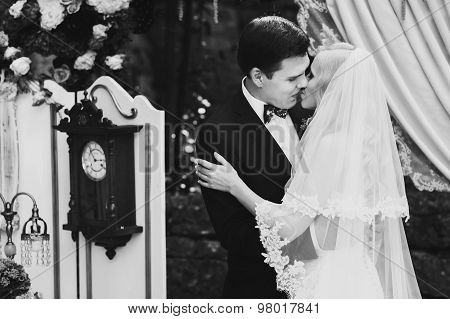 wonderful stylish rich happy bride and groom higing kissing at a wedding ceremony in garden near arch with flowers Montenegro black and white poster
