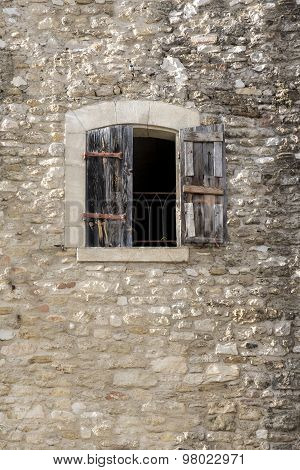 Building Made Of Natural Stone With A Window And Half-open Shutters