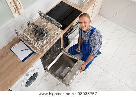 Worker With Toolbox Repairing Dishwasher