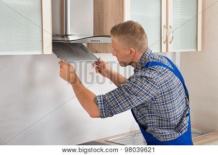 Repairman Repairing Kitchen Extractor Filter