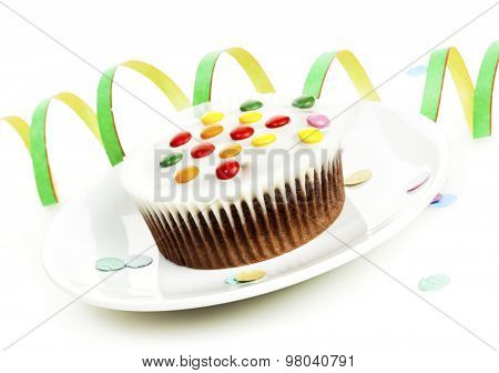 Cupcake with white cocolate and smarties on plate, streamer in background, tilted viewh