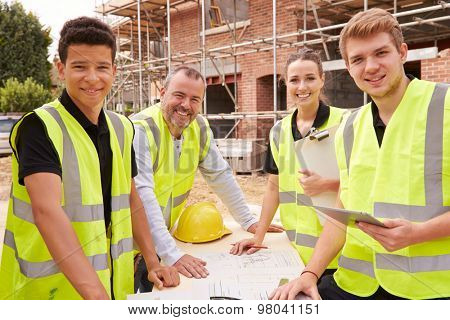 Portrait Of Builder On Building Site With Apprentices