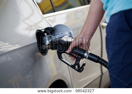 Silver car at gas station being filled with fuel