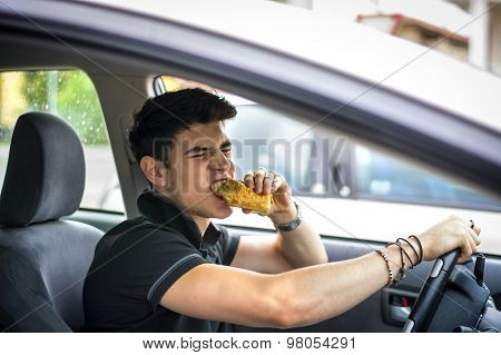 Young man driving his car while eating food