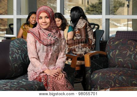 Portrait of young Muslim woman with headscarf inside college building on campus