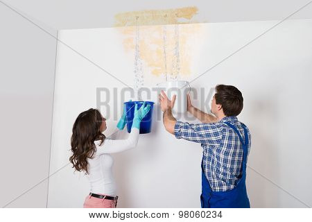 Woman And Repairman Collecting Water From Ceiling