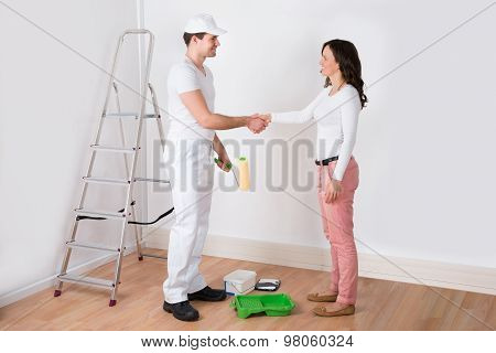 Woman Shaking Hands To Painter With Paint Roller At Home