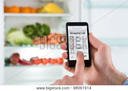 Person Hands Marking Shopping List On Mobile Phone Display