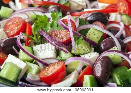 Greek salad in full frame.  Black olives, feta cheese, cucumber, cherry tomatoes, red onions and herbs.