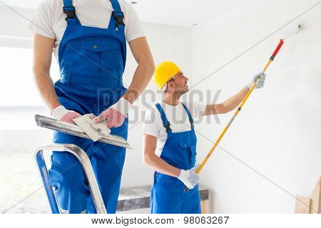 building, repair, teamwork and people concept - close up of two builders in hardhats and overalls with spatula and painting roller repairing room
