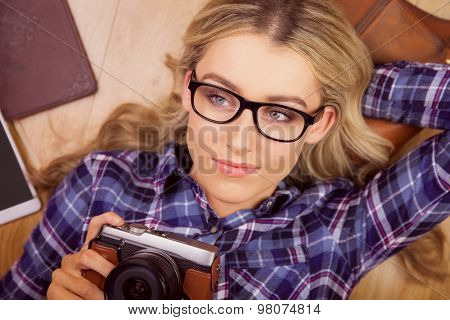 A blonde hipster lying on the floor taking a photo in her house