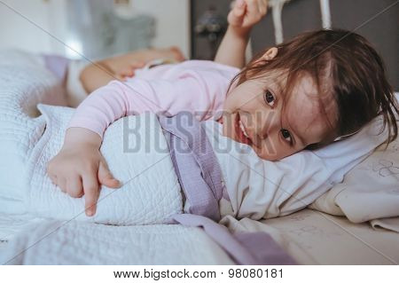 Little girl smiling lying over the bed