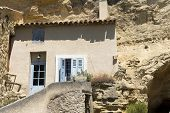 House facade in front of a cave in the mountain in the old village of Cadenet Provence south France Luberon Massif poster