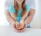 family, children, money, investments and people concept - close up of father and daughter hands holding euro money coins poster