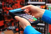 Hand of woman paying with contactless credit card with NFC technology in an electrical shop credit card reader payment terminal finance concept poster