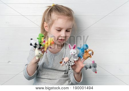 Lovely small girl with doll puppets on her hands, smiling and playing