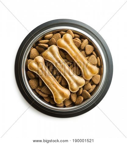 Dog chew bone and dry kibble dog food in bowl isolated on white background.