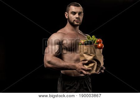 Shirtless Man Holding Bag With Healthy Vegetables Isolated On Black