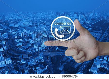 Telephone and mail icon button on finger over modern city tower street and expressway Contact us concept