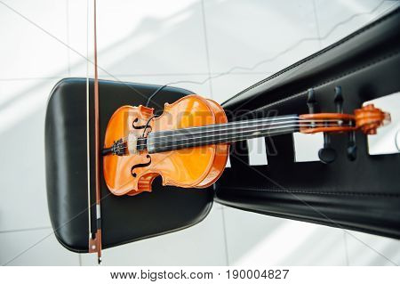 The classic violin was put on black chair.in blurry background .focus at violin .at studio's room prepare for practice.