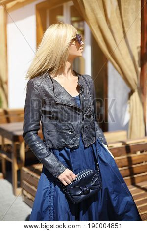 Outdoor summer smiling lifestyle portrait of pretty young woman with blue handbag. Long blond hairs blue jacket and dress.