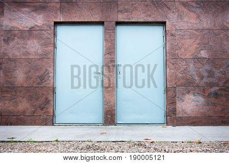 Twin steel door and granite wall background.
