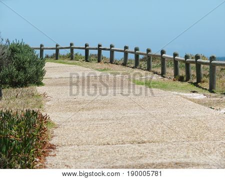 A CEMENT PATH WAY IN FORE GROUND, AND A WOODEN FENCE IN THE BACK GROUND