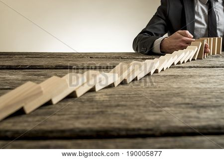 Businessman Interrupting Domino Effect