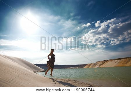 Young beautiful girl jumping on beach. She is dressed in denim shorts and a bra. Warm sunset light