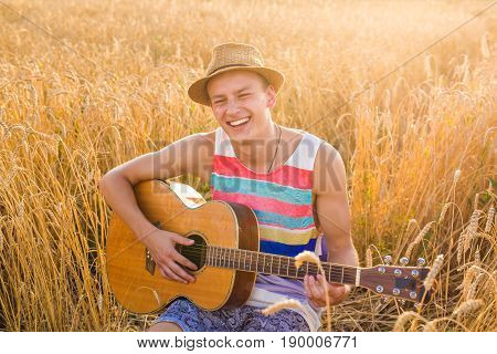 man outdoors playing acoustic guitar. A man is playing guitar in grass field at relax day with sun light.