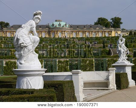 POTSDAM - GERMANY - SEPTEMBER, 2011: The palace of Sanssouci, residence of Prussian King Frederick II. White growth sculptures against historical architecture. Summer sunny weather, blue sky