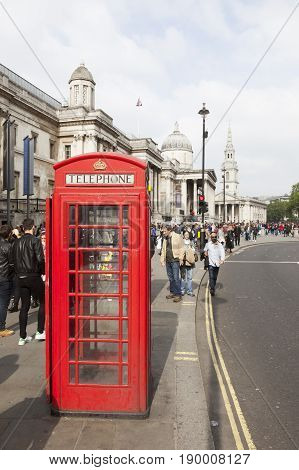 London United Kingdom 6 may 2017: red telephone box and a lot of people on the street near national gallery and trafalgar square in london