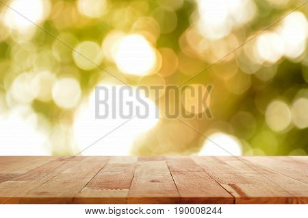 Wood table top on shinny sunlight natural green bokeh abstract background - can be used for montage or display your products