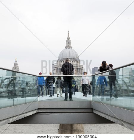 London United Kingdom 6 may 2017: people cross river thames on millennium bridge with st paul's cathedral in the background on overcast day in london