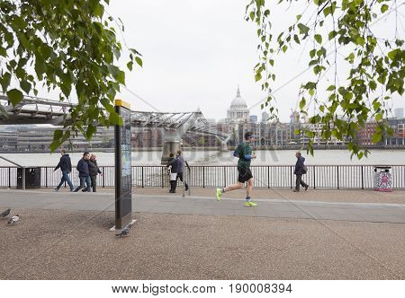 London United Kingdom 6 may 2017: people walk and jog near millennium bridge along river thames in london on overcast day in spring