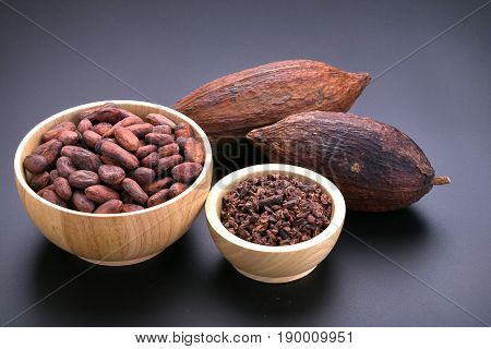 Chocolate Bar And Dried Cocoa Pod, Cocoa Nibs In Wooden Bowl On Black Background