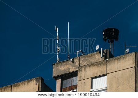 Civil defense siren on top of apartment building also known as air raid siren provides emergency warning of approaching danger such as tornadoes