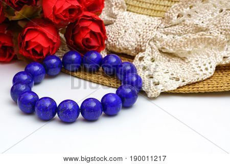 Beautiful high grade royal blue Lapis lazuli beads in bracelet with red roses and woven hat on white background