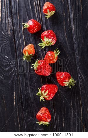 some raw ripe red strawberries on black background in studio