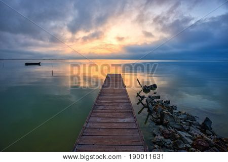 Wooden pier and rowboat at sea in summer