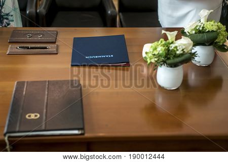 Civil german Wedding marriage Register with Pen, Bride and Groom Rings and Bouquet of Fresh Beautiful Flowers on Top of a Wooden Table.