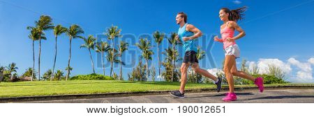 Sport runners running on summer park road banner - couple of young people jogging training cardio together - horizontal crop for landscape copyspace.