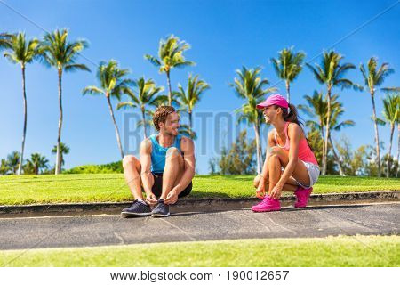 Runners tying running shoes getting ready to run. Runner woman and athlete man lacing shoe laces. Healthy lifestyle jogging motivation, happy healthy people.