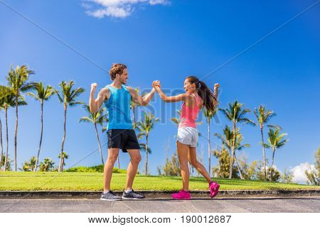 Challenge success runners people high fiving for fitness goal achievement. Athletes couple cheering clapping hands for winning a race. Outdoors sports lifestyle. Personal trainer encouraging girl.