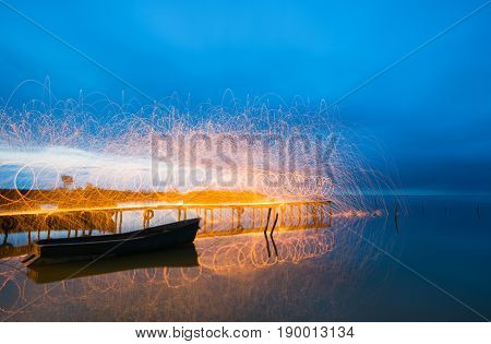 Freeze light using spinning burning steel wool near an old boat on the lake