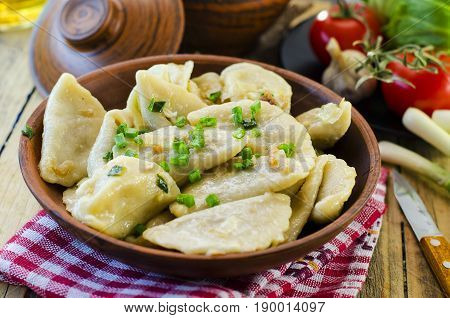 Dumplings with potato cabbage and meat in a clay plate
