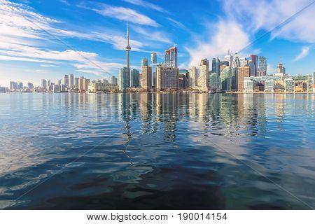Toronto skyline panorama over lake with urban architecture.